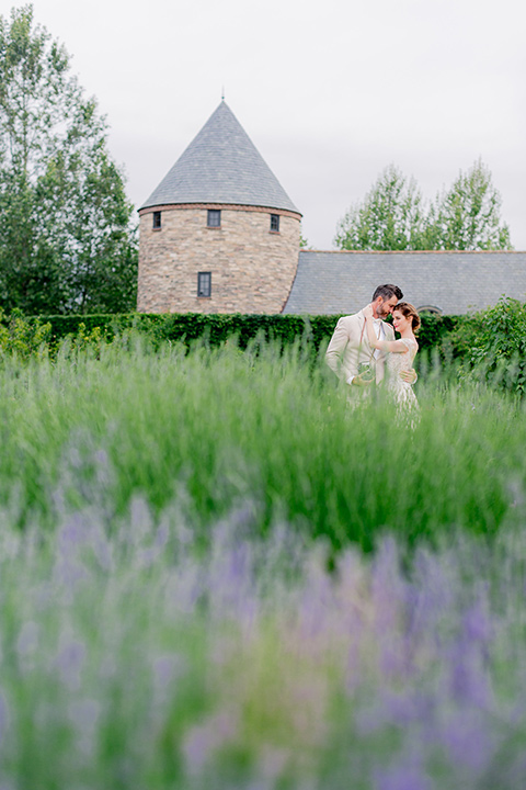 bride in a champagne and blush colored gown with the groom in a tan suit with a champagne bow tie by the lavender fields