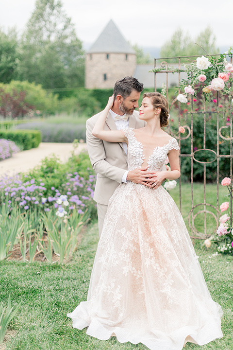 bride in a champagne and blush colored gown with the groom in a tan suit with a champagne bow tie in the garden