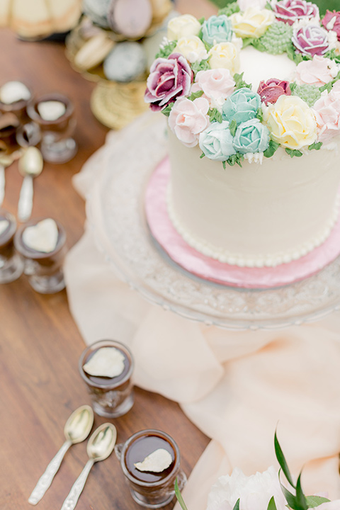 white cake with a rose colored trim and floral decor