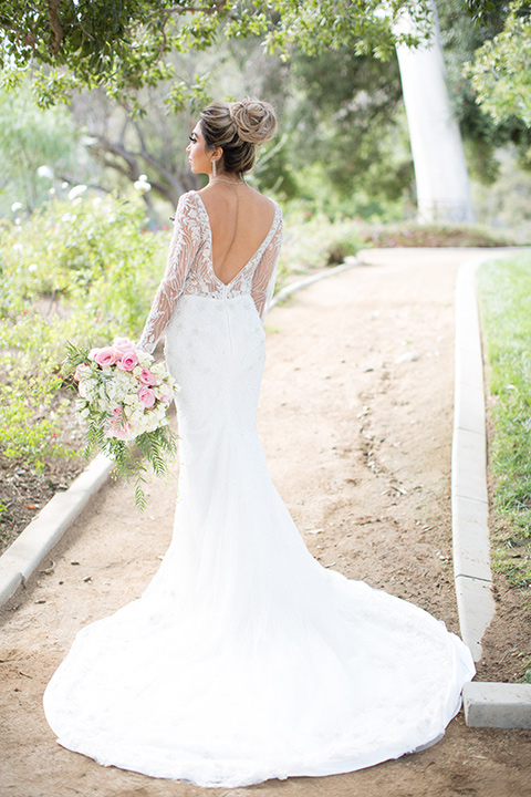 bride in a long sleeved gown with a satin underlay and hair up in a top knot bun