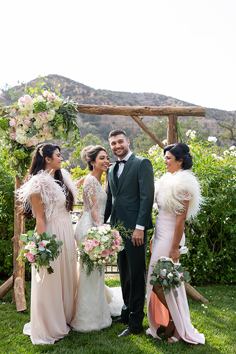 bride in a lace gown with long sleeves and a bouquet of white and pink florals bridesmaids in light pink gowns and the groom in a dark green suit