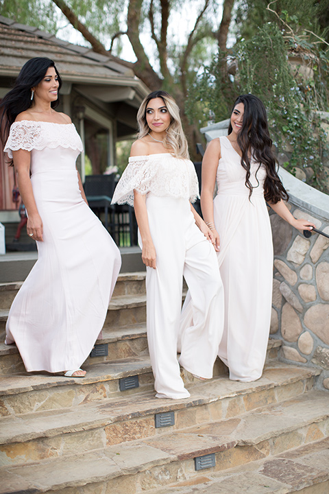 bride in a white off the shoulder jumpsuit and bridesmaids in pink gowns