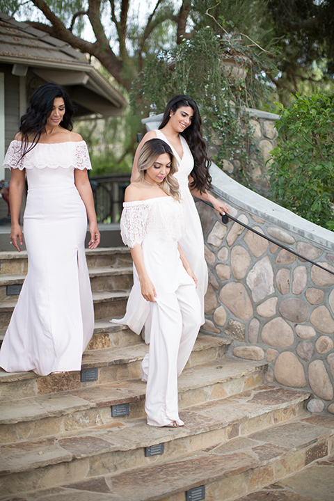 bride in a white jumpsuit and bridesmaids in pink gowns