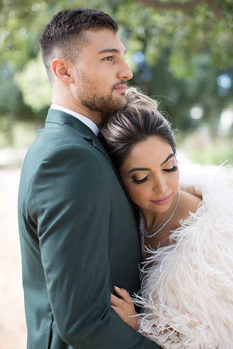 bride in a fur cape and hair in a high bun with her head resting on her groom in a green suit