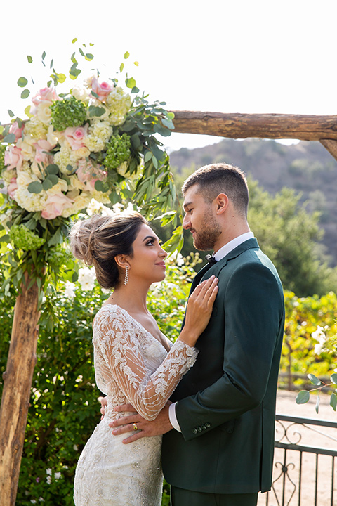 bride in a long sleeved gown with a satin underlay and hair up in a top knot bun groom in a dark green suit