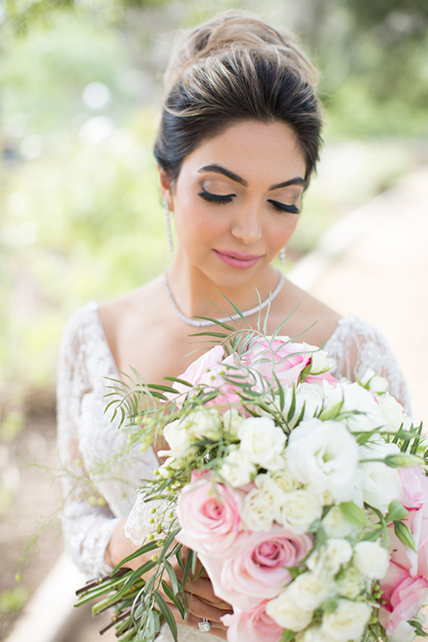 bride in a lace gown with long sleeves and a bouquet of white and pink florals