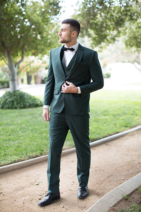 groom in a green suit with a black bow tie