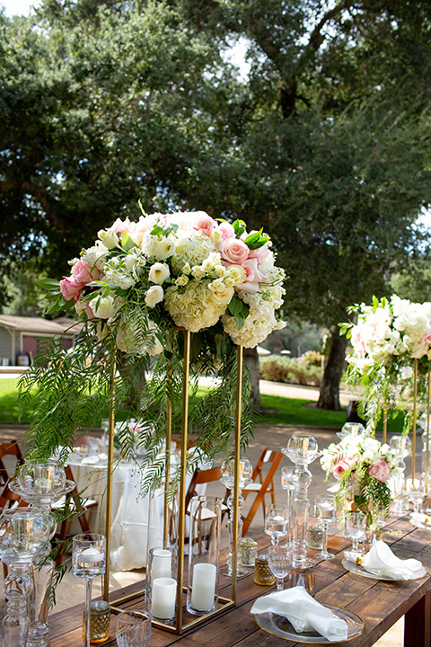 tall floral arrangements with candles on wooden tables