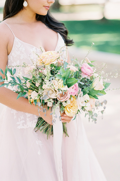 bride in a blush colored gown with thin straps and a sweetheart neckline