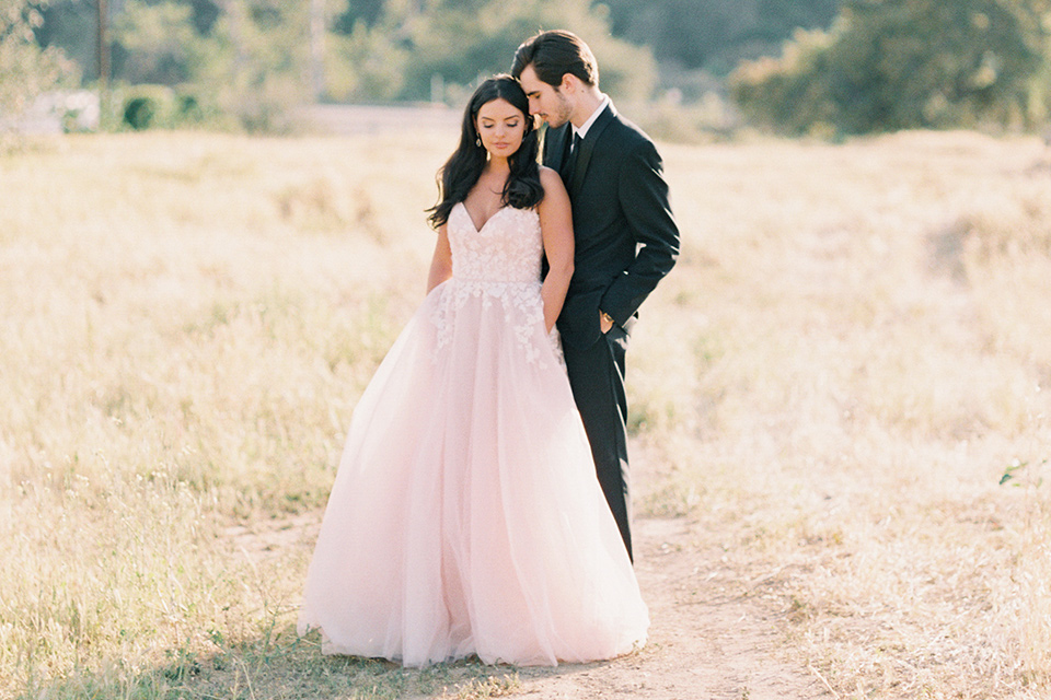 bride in a blush tulle ballgown with a low back and a sweetheart neckline and the groom in a black tuxedo with a long black tie sitting on a couch