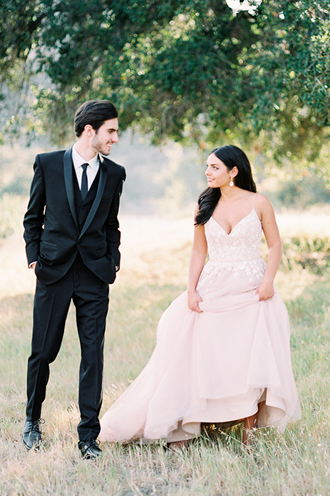 bride in a blush bridal gown with thin straps and a sweetheart neckline and the groom in a black shawl lapel tuxedo with a black long tie