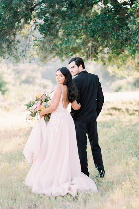 bride in a blush colored gown with thin straps and a sweetheart neckline and the groom in a black shawl lapel tuxedo with a black long tie