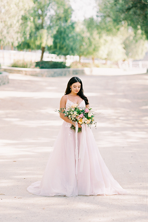 bride in a blush bridal gown with thin straps and a sweetheart neckline