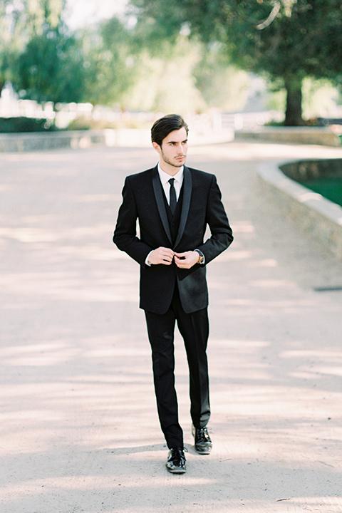groom in a black shawl lapel tuxedo with a black long tie