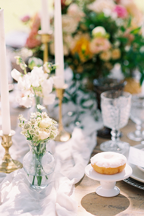 colorful garden flowers and tall candles with colorful crystal and white linens