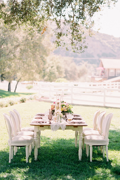 wooden table with wooden chairs and candles with florals and linens
