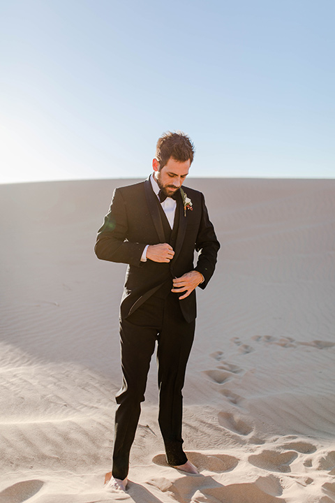 Glamis-Engagement-Shoot-Groom-alone-wearing-a-black-tuxedo-with-a-velvet-bow
