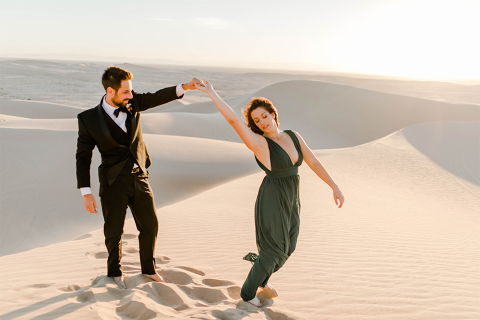 Glamis-Engagement-Shoot-bride-and-groom-dancing-bride-in-a-deep-green-flowing-dress-with-a-plunging-neckline-groom-in-a-black-tuxedo-with-navy-blue-velvet-bow-tie