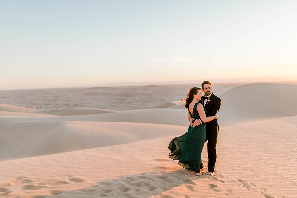 Glamis-Engagement-Shoot-bride-and-groom-holding-eachother-bride-in-a-deep-green-flowing-dress-with-a-plunging-neckline-groom-in-a-black-tuxedo-with-navy-blue-velvet-bow-tie
