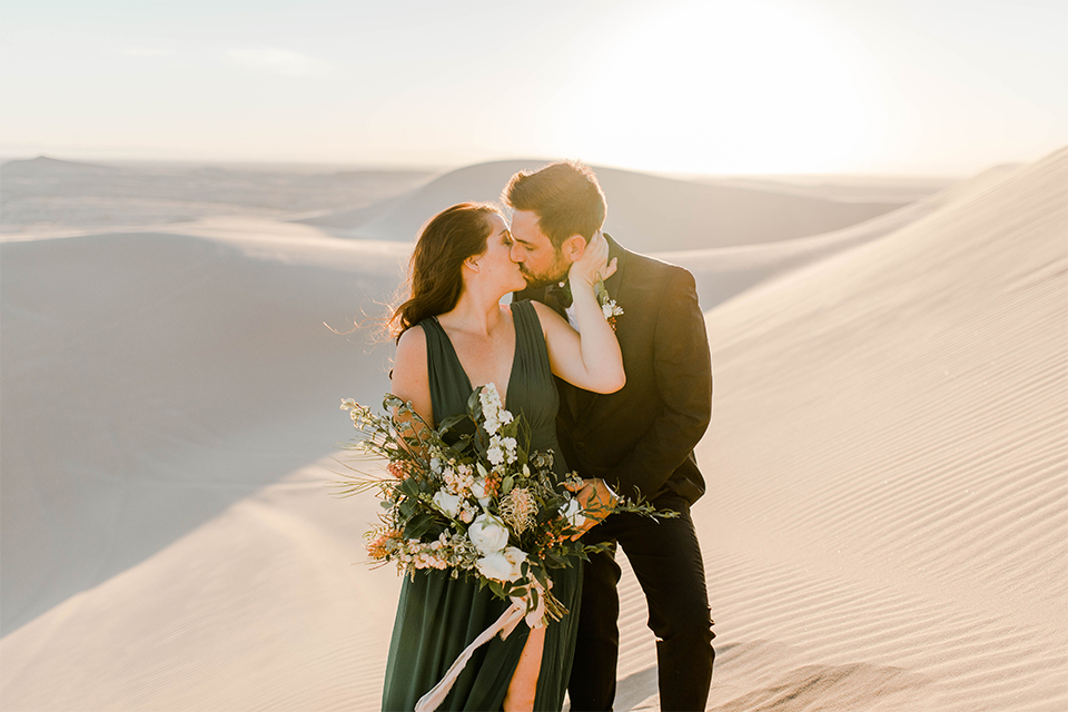 Glamis-Engagement-Shoot-bride-and-groom-holding-hands-bride-in-a-deep-green-flowing-dress-with-a-plunging-neckline-groom-in-a-black-tuxedo-with-navy-blue-velvet-bow-tie