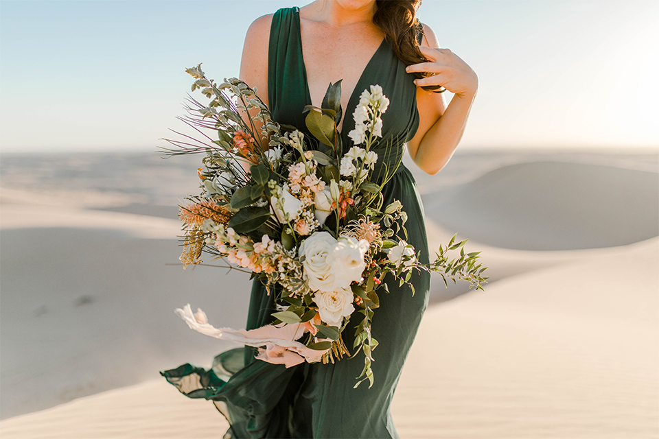 Glamis-Engagement-Shoot-close-up-on-bride-bride-in-a-deep-green-flowing-dress-with-a-plunging-neckline-groom-in-a-black-tuxedo-with-navy-blue-velvet-bow-tie