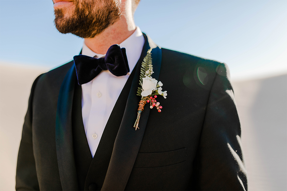 Glamis-Engagement-Shoot-closeup-on-groom-bride-in-a-deep-green-flowing-dress-with-a-plunging-neckline-groom-in-a-black-tuxedo-with-navy-blue-velvet-bow-tie