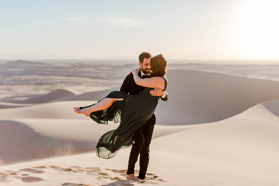 Glamis-Engagement-Shoot-groom-holding-bride-bride-in-a-deep-green-flowing-dress-with-a-plunging-neckline-groom-in-a-black-tuxedo-with-navy-blue-velvet-bow-tie