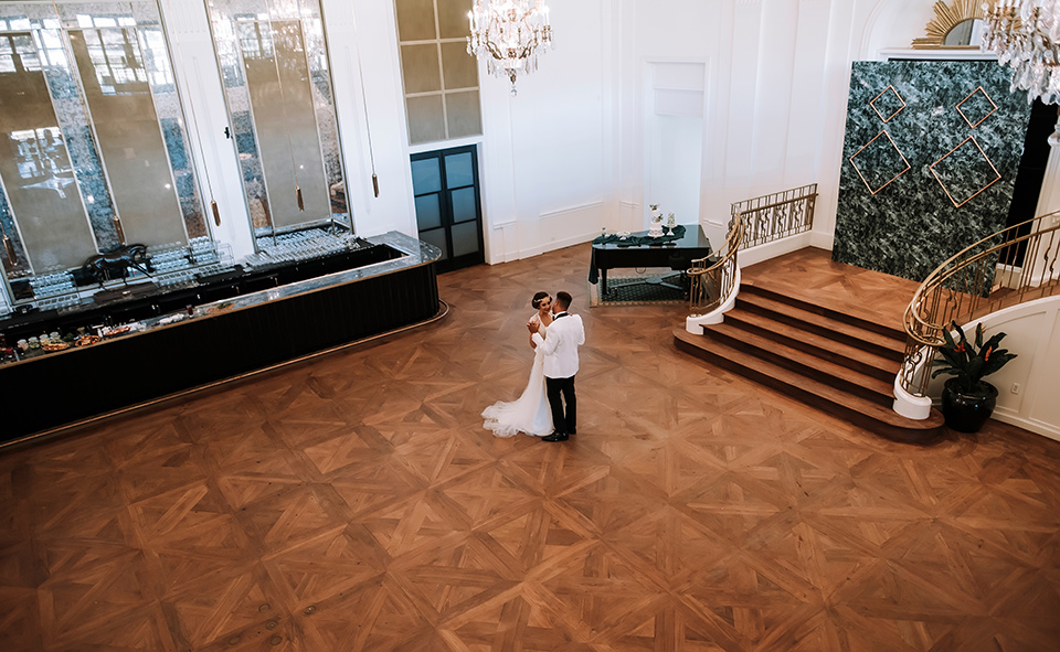 bride and groom dancing in a big hall