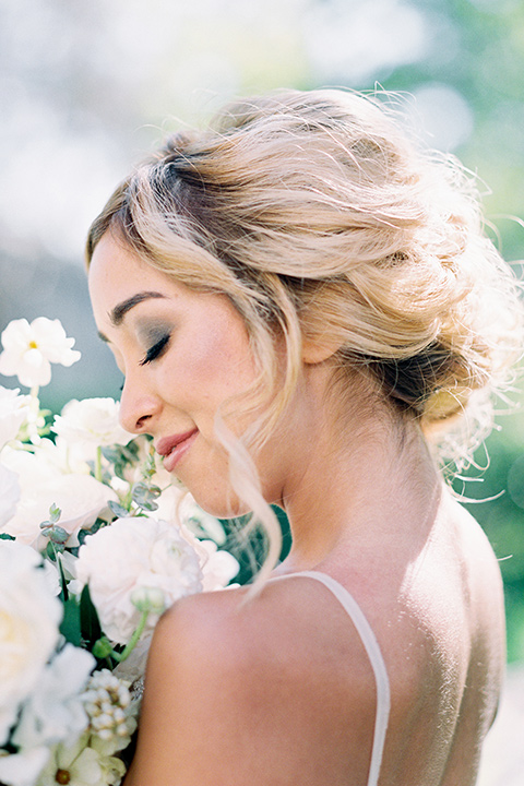 bride wearing a tulle ballgown with thin straps and her hair in a loose braided bun