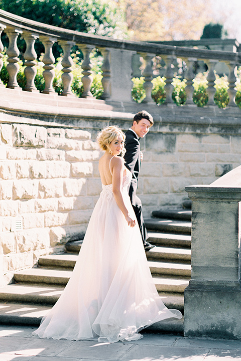 bride wearing a tulle ballgown with thin straps and her hair in a loose braided bun with a peony and rose bouquet and the groom in a black tuxedo and a black bow tie walking up the stairs