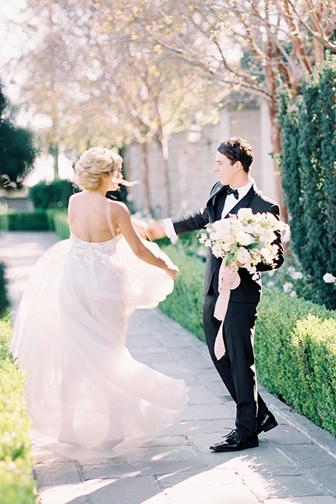 bride wearing a tulle ballgown with thin straps and her hair in a loose braided bun and the groom in a black tuxedo with a black bow tie twirling