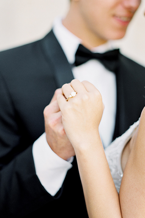 bride wearing a tulle ballgown with thin straps and her hair in a loose braided bun with a peony and rose bouquet and the groom in a black tuxedo and a black bow tie close up and holding hands