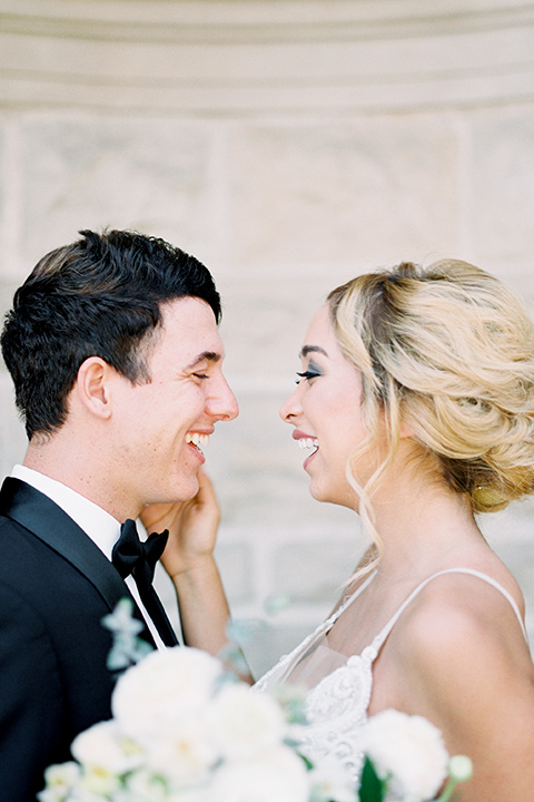 bride wearing a tulle ballgown with thin straps and her hair in a loose braided bun and the groom in a black tuxedo with a black bow tie smiling at each other