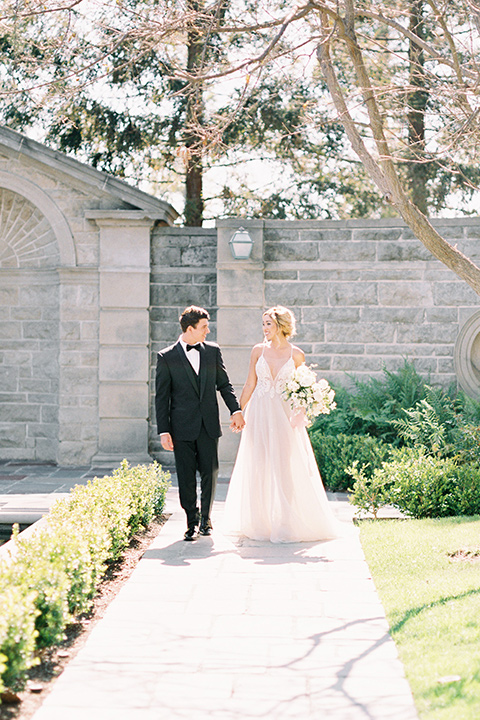 bride wearing a tulle ballgown with thin straps and her hair in a loose braided bun with a peony and rose bouquet and the groom in a black tuxedo and a black bow tie walking down a walk way holding hands