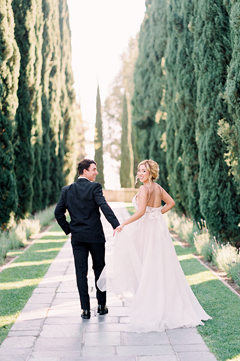 bride wearing a tulle ballgown with thin straps and her hair in a loose braided bun with a peony and rose bouquet and the groom in a black tuxedo and a black bow tie walking away