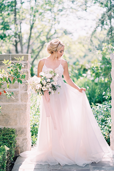 bride wearing a tulle ballgown with thin straps and her hair in a loose braided bun with a peony and rose bouquet