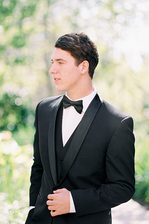 the groom in a black tuxedo and a black bow tie close up