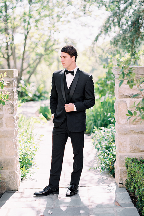 the groom in a black tuxedo with a black bow tie standing by archway