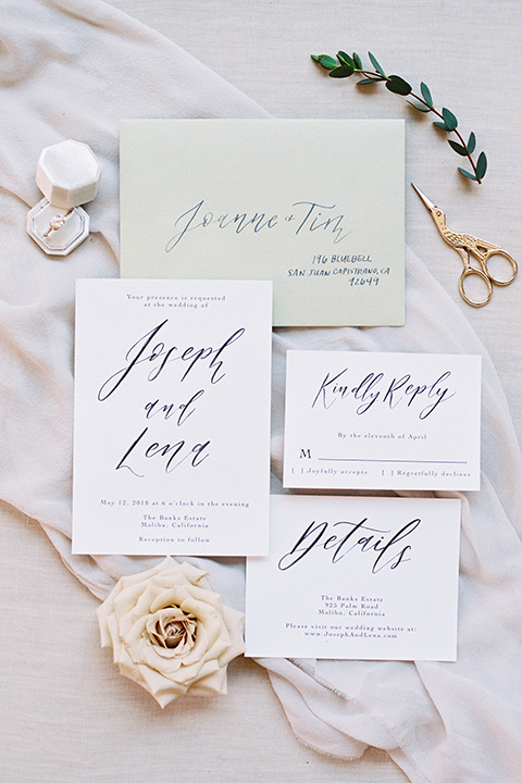 white invitations with calligraphy and pink flowers