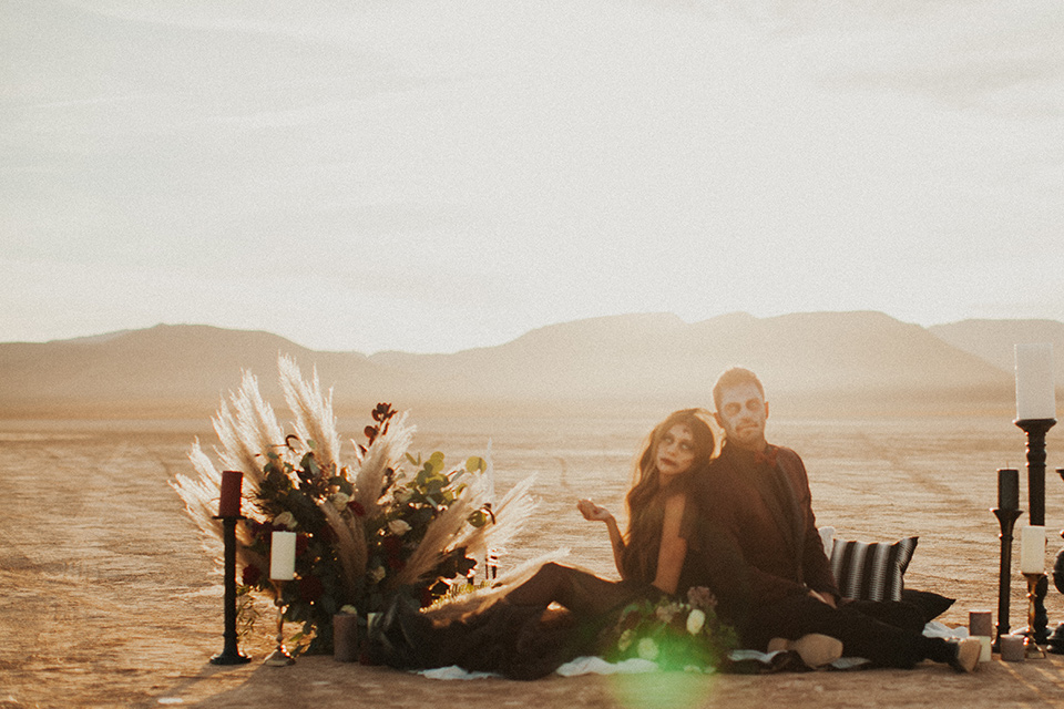 halloween shoot with the bride in a black and burgundy tulle gown with a black veil and skeleton makeup and the groom in a burgundy tuxedo with a black shirt and burgundy bow tie sitting on a carpet in the desert with candles and florals
