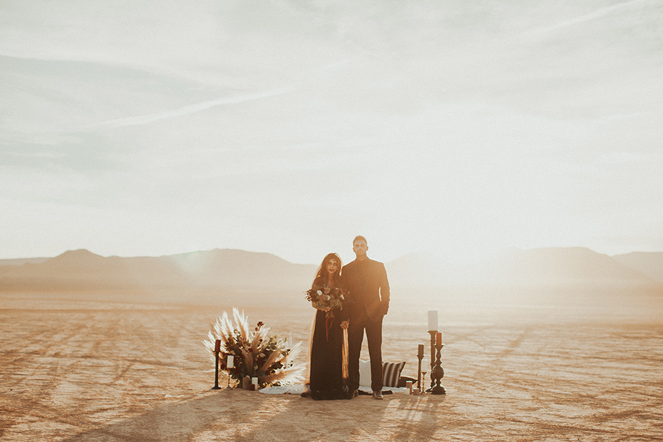 halloween shoot with the bride in a black and burgundy tulle gown with a black veil and skeleton makeup and the groom in a burgundy tuxedo with a black shirt and burgundy bow tie