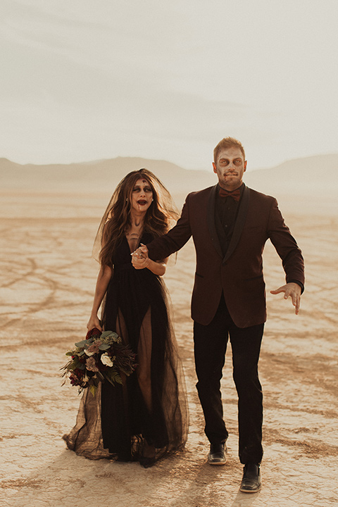 Halloween shoot with the bride in a skeleton makeup with a burgundy and black tulle gown and a black veil and the groom is in a burgundy tuxedo with a black shirt and burgundy bow tie