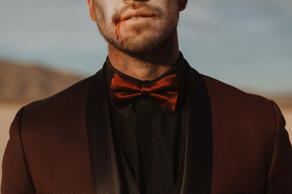 Halloween-Shoot with the groom in a burgundy tuxedo with a black shirt and burgundy bow tie