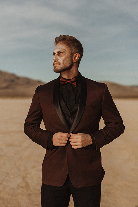 Halloween shoot with the groom in a burgundy tuxedo with a black trim, a black shirt, and a burgundy bow tie sitting down