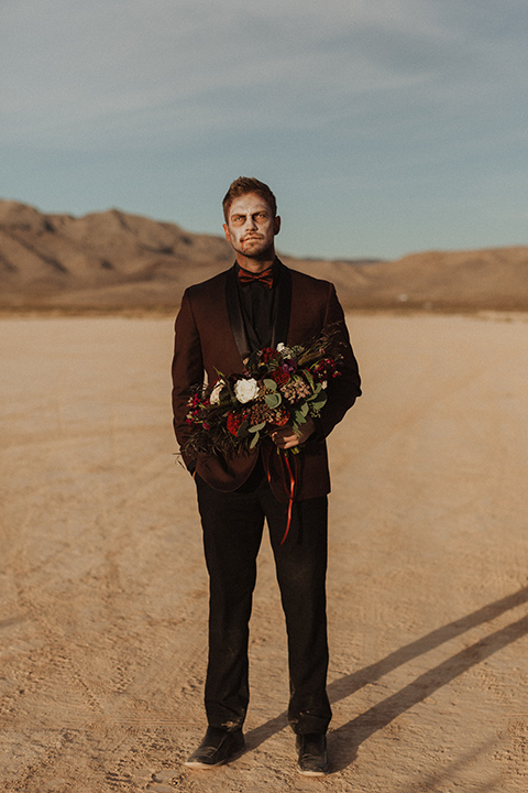 Halloween shoot with the groom is in a burgundy tuxedo with a black shirt and burgundy bow tie