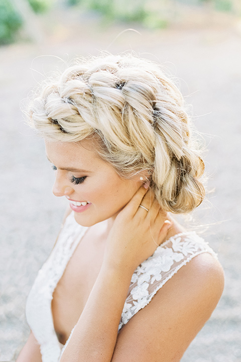 the bride in a white lace form fitting gown with an illusion gown with a deep v and her hair in a braided loose bun