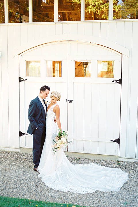 the bride in a white lace form fitting gown with an illusion gown with a deep v and her hair in a braided loose bun groom in a dark blue suit with a tan tie by barn door