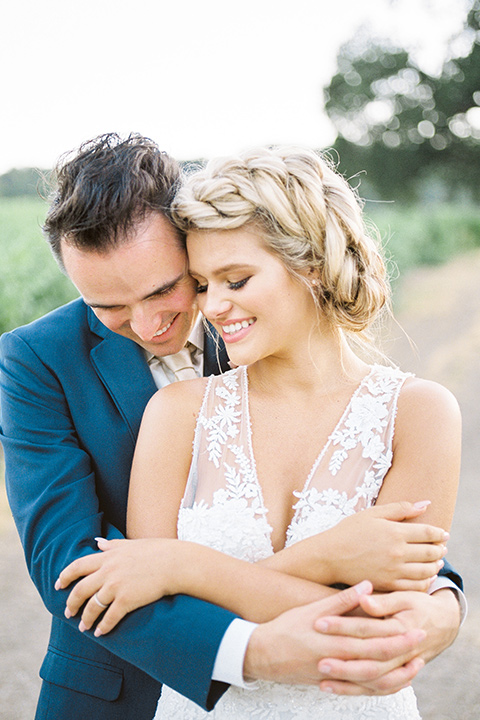 the bride in a white lace form fitting gown with an illusion gown with a deep v and her hair in a braided loose bun groom in a dark blue suit with a tan tie, groom holding bride