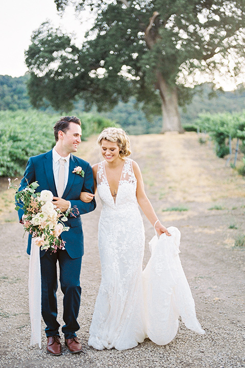 the bride in a white lace form fitting gown with an illusion gown with a deep v and her hair in a braided loose bun holding her bouquet and the groom in a blue suit with a tan tie walking down a path
