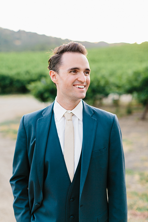 the groom in a blue suit with a tan tie